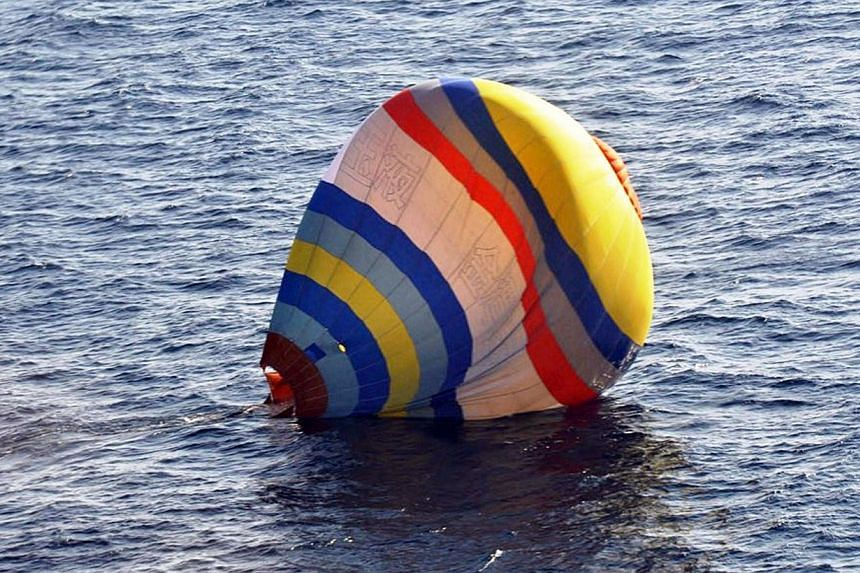 A hot-air balloon which was carrying a Chinese man lands on the water, south of the disputed islets known as the Senkaku islands in Japan and Diaoyu islands in China, in the East China Sea, on Wednesday, Jan 1, 2014. The man was rescued by the Japan