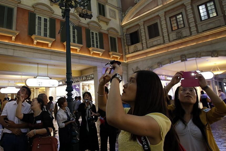 Visitors take photos inside the Venetian Macao resort in Macau, on Oct 29, 2013. Macau's gambling revenue jumped 18.6 per cent to a record US$45 billion (S$56.8 billion) in 2013, official figures showed on Thursday, Jan 2, 2014, cementing the city's