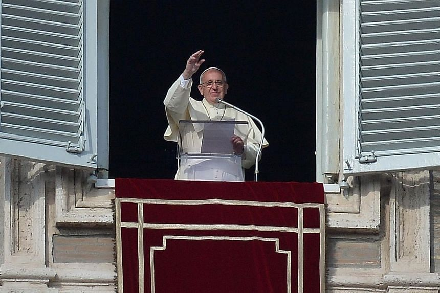 Pope Francis greets the crowd from the window of the apostolic palace overlooking St.Peter's square during his Sunday Angelus prayer, on Dec 29, 2013, at the Vatican.More than 6.6 million people attended events with Pope Francis at the Vatican