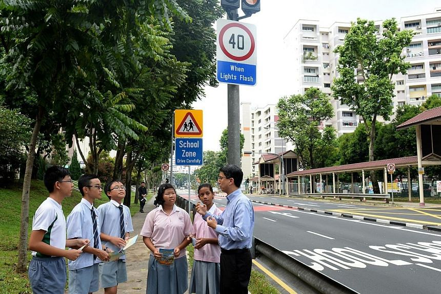 Parliamentary Secretary for Transport Muhammad Faishal Ibrahim (right) talking to five students near Shuqun Primary School in Jurong West on Nov 14, 2013. Dr Faishal mentioned that motorists are driving more carefully in school zones with enhanc