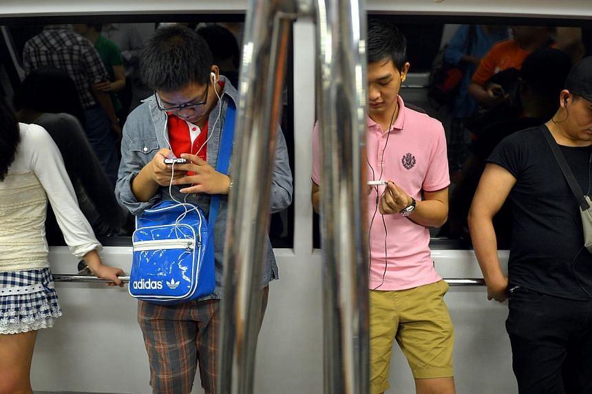 People using their smartphones while on the train. The study on mobile device usage involved over 235 students who were questioned on their use of smartphones, tablets and other devices by a team led by Prof Vivien Lim.