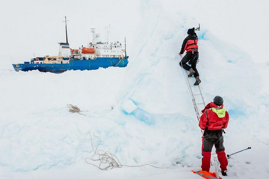 Ben Maddison and Ben Fisk working on Dec 31, 2013, to place a wind indicator atop an ice feature near the MV Akademik Shokalskiy (left), still stuck in the ice off East Antarctica, as the ship waits for a possible helicopter rescue. Sea ice delayed a