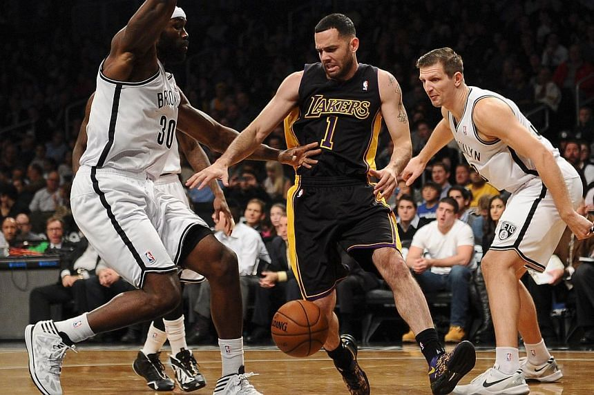Jordan Farmar #1 of the Los Angeles Lakers and Mirza Teletovic #33 and Reggie Evans #30 of the Brooklyn Nets battle for a loose ball during the second quarter at Barclays Center on Nov 27, 2013 in the Brooklyn borough of New York City. Los Angeles La