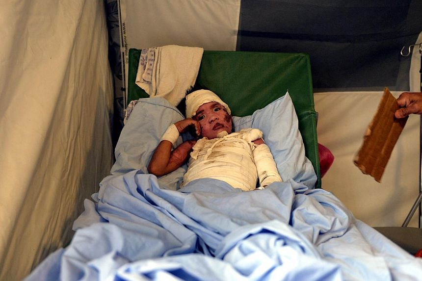 Eight-year-old Recto Villanege lies inside the International Commission for The Red Cross emergency hospital in Basey. Recto was scalded by boiling water and was sent to the hospital for treatment. All patients receive free treatment at the hospital