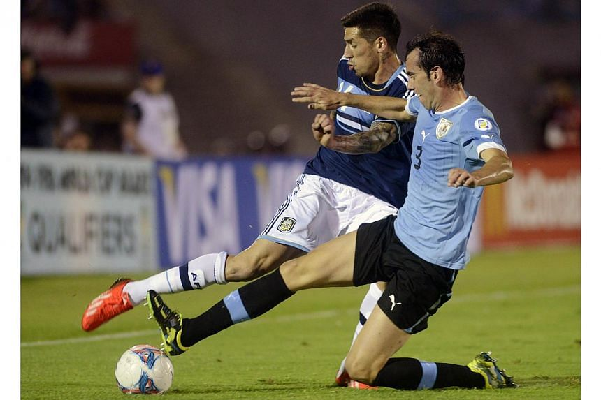 Argentina's Jose Sosa (left) fights for the ball with Uruguay's Diego Godin during their 2014 World Cup qualifying soccer match in Montevideo on Oct 15, 2013. Atletico Madrid on Wednesday announced an agreement that will see Argentinian international