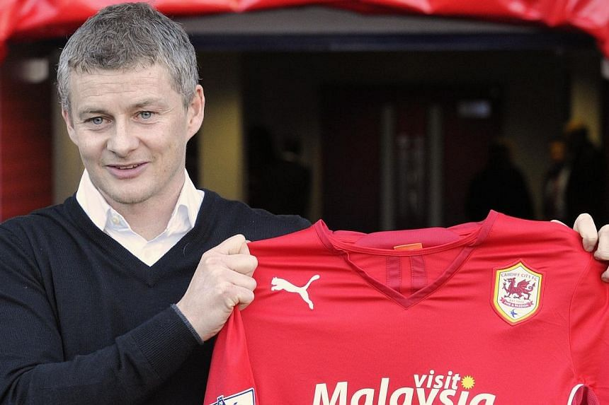 Former Manchester United striker Ole Gunnar Solskjaer holds a club shirt as he is officially unveiled as the new manager of English Premier League team Cardiff City at their stadium in Cardiff, Wales, on Jan 2, 2014. -- PHOTO: REUTERS