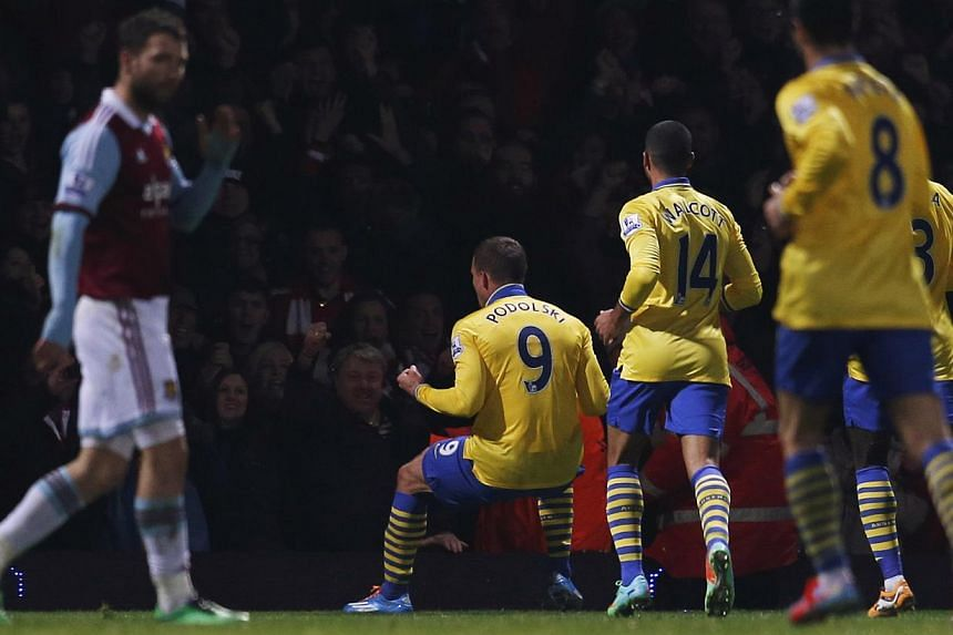 Arsenal's Lukas Podolski (centre) celebrates after scoring a goal against West Ham United during their English Premier League soccer match at the Boleyn Ground in London on Dec 26, 2013. Players from Premier League leaders Arsenal sent stricken