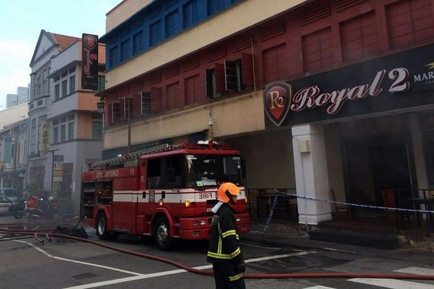 Fire engines were on hand to put out the blaze at a coffeeshop on the corner of Mosque Street and Eu Tong Sen Street. -- ST PHOTO: NG SOR LUAN