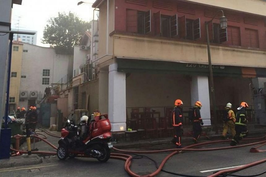 Fire engines were on hand to put out the blaze at a coffeeshop on the corner of Mosque Street and Eu Tong Sen Street.-- ST PHOTO:NG SOR LUAN