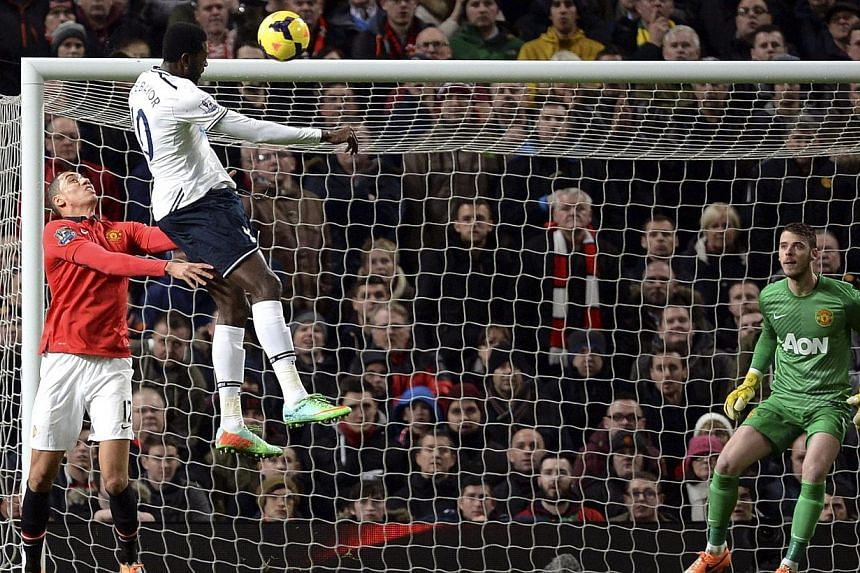 Tottenham Hotspur's Emmanuel Adebayor (centre) heads and scores his goal against Manchester United during their English Premier League soccer match at Old Trafford in Manchester, northern England, on Jan 1, 2014. Adebayor's return to form has ensured
