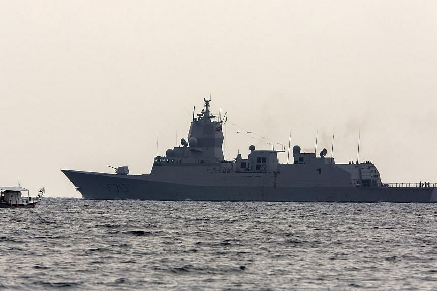 The Norwegian frigate Helge Ingstad sails past a fishing boat as it leaves the port of Limassol in the east Mediterranean island of Cyprus for waters off Syria on Jan 3, 2014. The Vessels areheaded towards Syria to escort a delayed shipment of