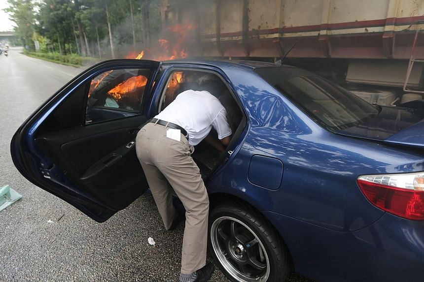 Two people were sent to the National University Hospital (NUH) after the car they were in burst into flames along the Bukit Timah Expressway (BKE).-- TNP PHOTO:JONATHAN CHOO