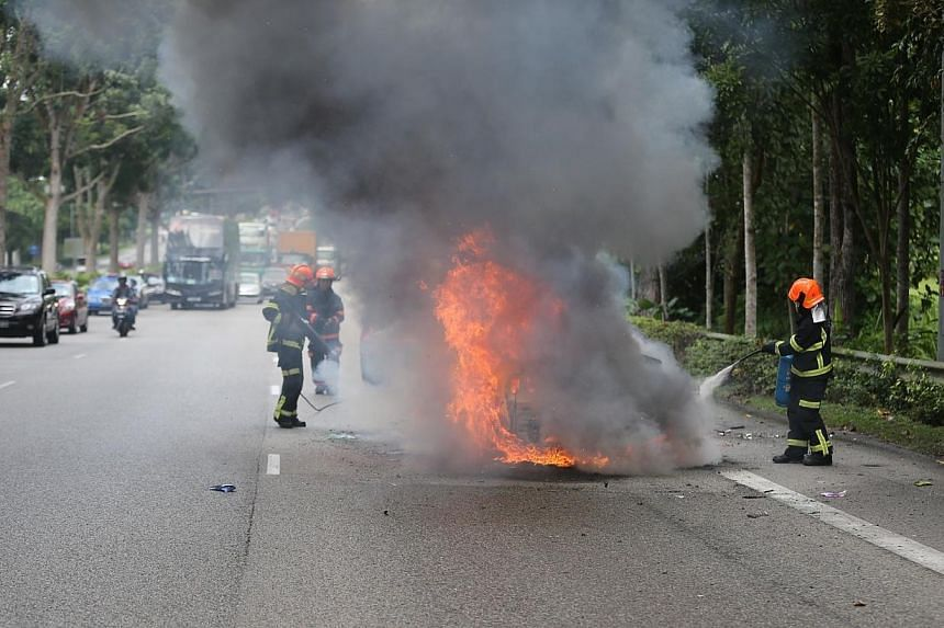 Two people were sent to the National University Hospital (NUH) after the car they were in burst into flames along the Bukit Timah Expressway (BKE). -- TNP PHOTO: JONATHAN CHOO