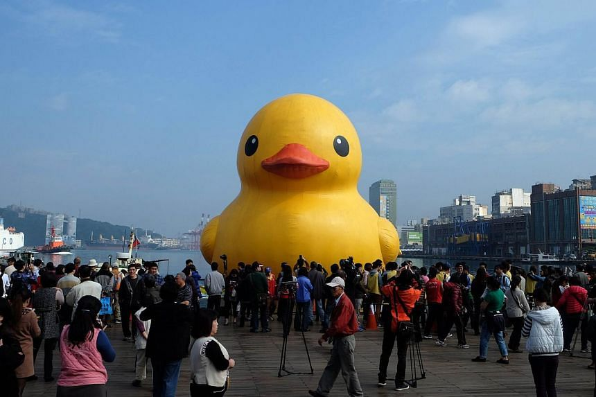 Visitors look at an 18m bath toy duck replica created by Dutch artist Florentijn Hofman as it floats its repair in Keelung Harbor after it was repaired on Jan 3, 2014. The giant yellow duck on display in a northern Taiwan port exploded just hours bef