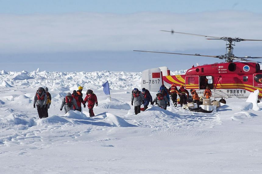 This photo released by the Australian Antarctic Division on Jan 2, 2014, shows passengers who spent Christmas and New Year trapped on the ice-bound Russian research vessel Akademik Shokalskiy in Antarctica disembarking from a rescue helicopter from t