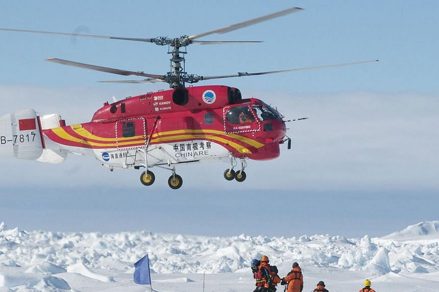 This image taken by expedition doctor Andrew Peacock of www.footloosefotography.com on Jan 2, 2014, shows a helicopter from the nearby Chinese ice-breaker Xue Long above passengers from the stranded Russian ship MV Akademik Shokalskiy as the first he