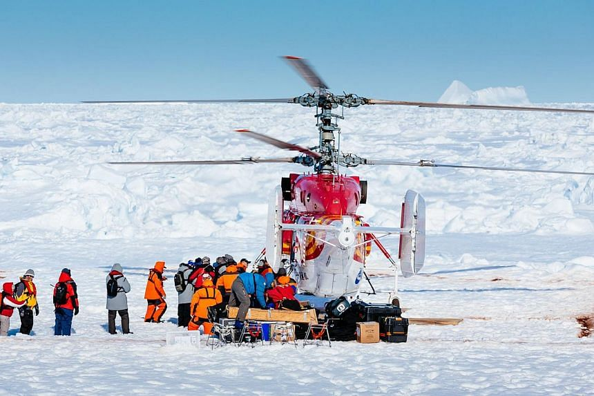 This image taken by expedition doctor Andrew Peacock of www.footloosefotography.com on Jan 2, 2014, shows a helicopter from the nearby Chinese ice-breaker Xue Long picking up the first batch of passengers from the stranded Russian ship MV Akademik Sh