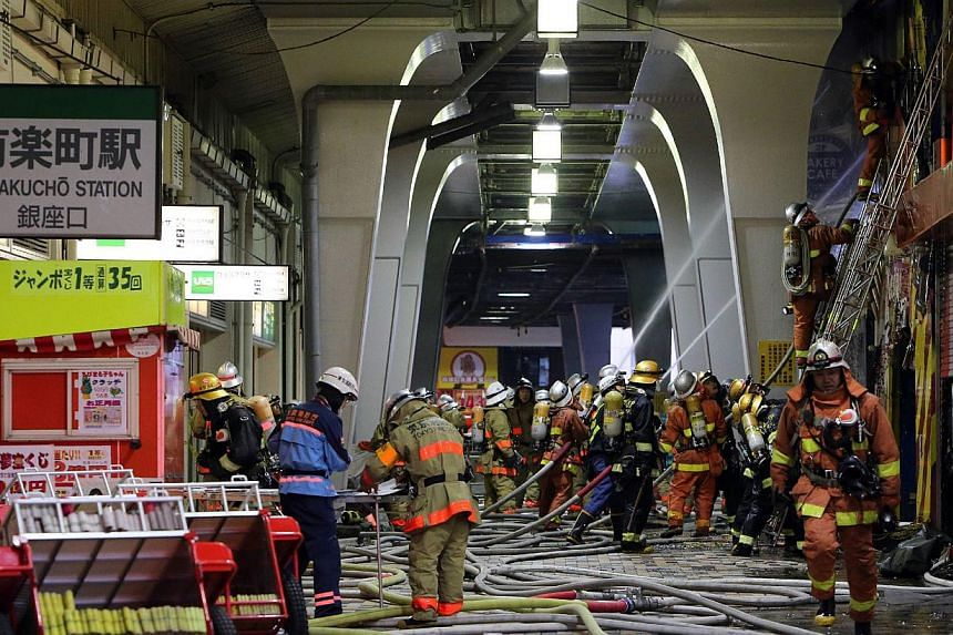 Firefighters spray water following a fire in a commercial building next to railway tracks near the Tokyo station on Jan 3, 2013. The fire stopped Japan's bullet train system, stalling tens thousands of passengers as they start returning home from New