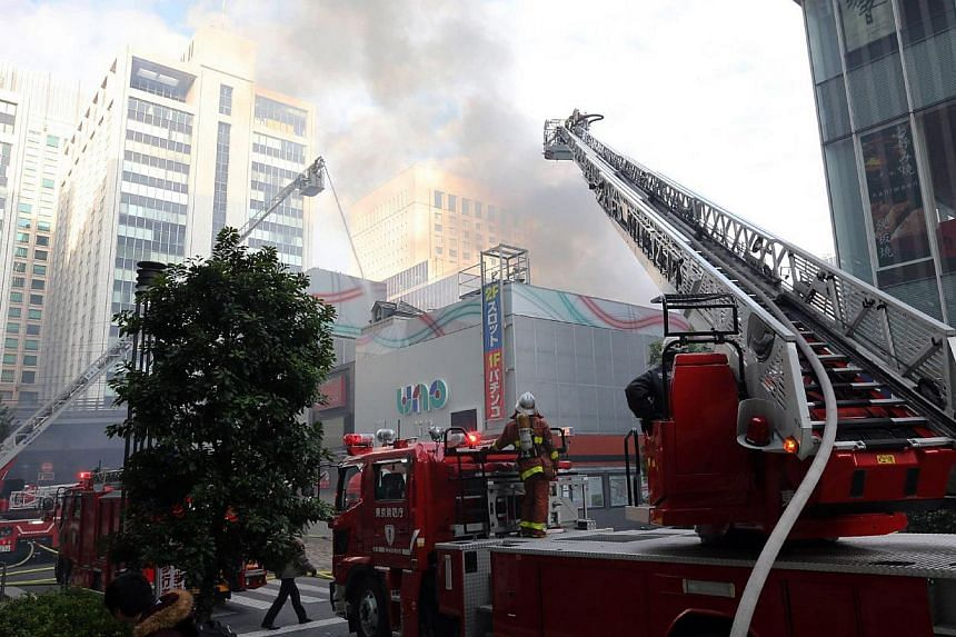 Firefighters spray water as smoke rises from a commercial buildings next to railway tracks near the Tokyo station on Jan 3, 2013. The fire stopped Japan's bullet train system, stalling tens thousands of passengers as they start returning home from Ne