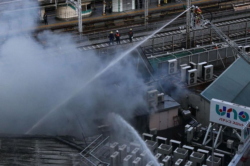 Firefighters spray water as smoke rises from commercial building next to railway tracks near the Tokyo station on Jan 3, 2013. The fire stopped Japan's bullet train system, stalling tens thousands of passengers as they start returning home from New Y
