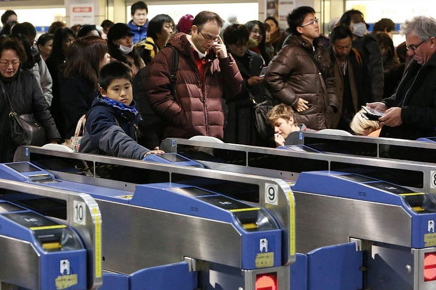 Passengers wait for the bullet train to resume service at the Tokyo station on Jan 3, 2014, after a fire broke out in a commercial building next to railway tracks near the Tokyo station. The fire stopped Japan's bullet train system, stalling tens tho