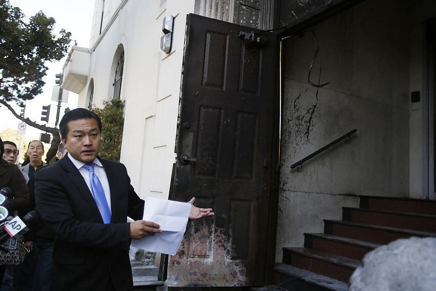 Wang Chuan, a spokesman for the Chinese consulate in San Francisco, points to a damaged door during a news conference after an unidentified person set fire in San Francisco, California Jan 2, 2014. An arsonist severely damaged the front door of China