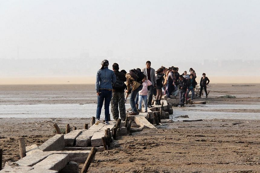 People walking on an ancient stone bridge on the dried up lakebed of Poyang lake in Jiujiang, east China's Jiangxi province, on Nov 2, 2013.A stone bridge dating back to the Ming dynasty has been discovered after water levels plunged at the lak