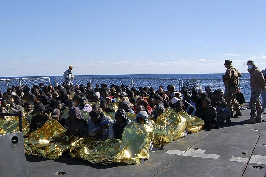 Migrants sit in a Marina Militare vessel during a rescue operation by Italian navy off the coast of the south of the Italian island of Sicily, on Jan 2, 2014. The Italian navy said on Friday it had rescued in 24 hours more than 1,000 migrants attempt