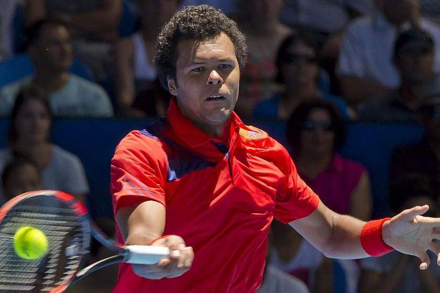 Jo-Wilfried Tsonga of France hits a return against Daniel Munoz-De La Nava of Spain during their eleventh session men's singles match on day seven of the Hopman Cup tennis tournament in Perth, on Jan 3, 2014. France will play in their third Hopm