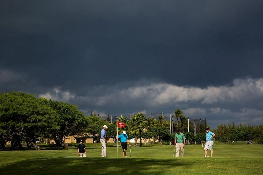 United States President Barack Obama, Mr Max Key, Mr Marvin Nicholson, and New Zealand Prime Minister John Key are seen on the green of the second hole of the Kaneohe Klipper Golf Course at Marine Corps Base Hawaii on Jan 2, 2014. -- PHOTO: AFP
