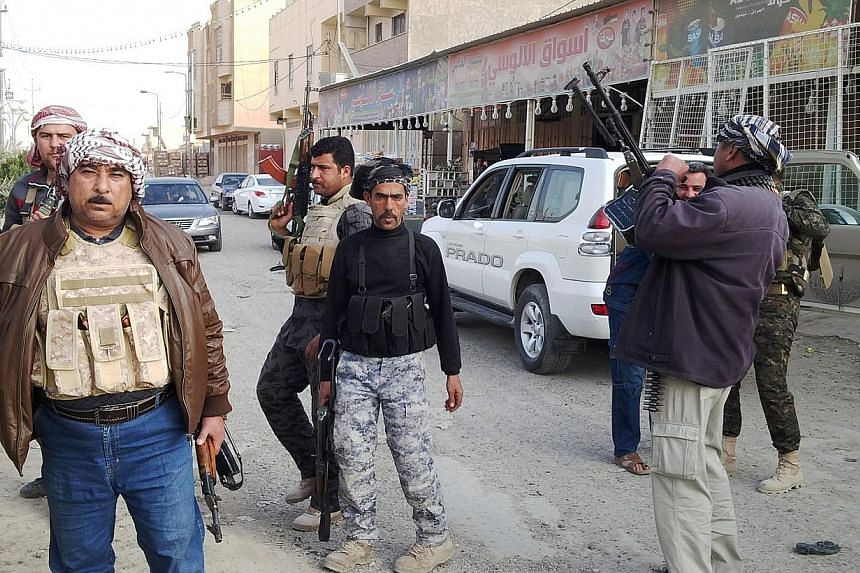 Armed tribesmen and Iraqi police stand guard in a street as clashes rage on in the Iraqi city of Ramadi, West of Baghdad, on Jan 2, 2014.Iraqi forces backed by tribesmen battled jihadists on Thursday after they seized parts of two Sunni-majorit