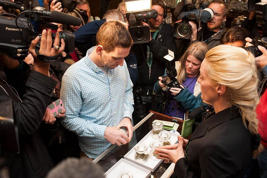 Mr Sean Azzariti, a veteran of the Iraq war, prepares to make the first legal recreational marijuana purchase in Colorado from advocate Betty Aldworth at the 3-D Denver Discrete Dispensary on Jan 1, 2014 in Denver, Colorado. Marijuana enthusiast