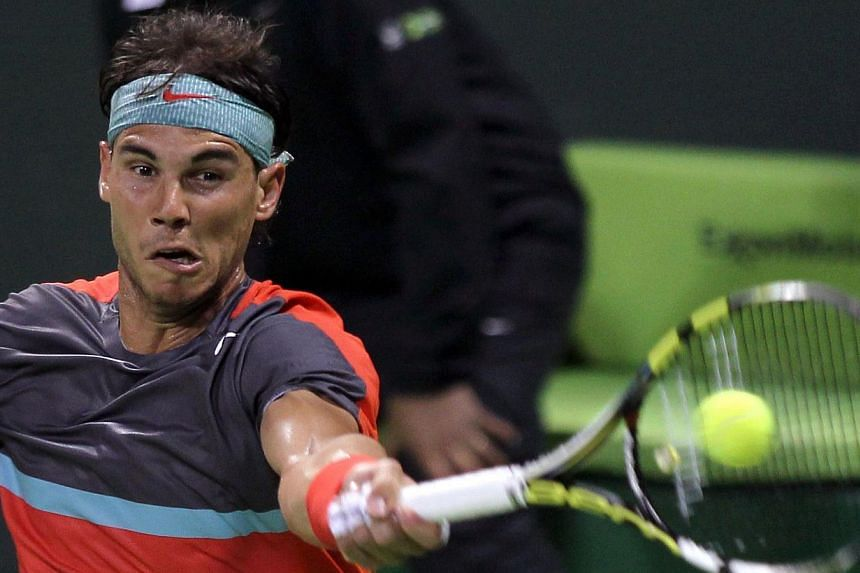 Spain's Rafael Nadal returns the ball to Latvia's Ernests Gulbis during their tennis match in Qatar's ExxonMobil Open in Doha on Jan 2, 2014.Nadal showed his trademark grit and determination on Thursday as he reached the semi-finals of the Qata