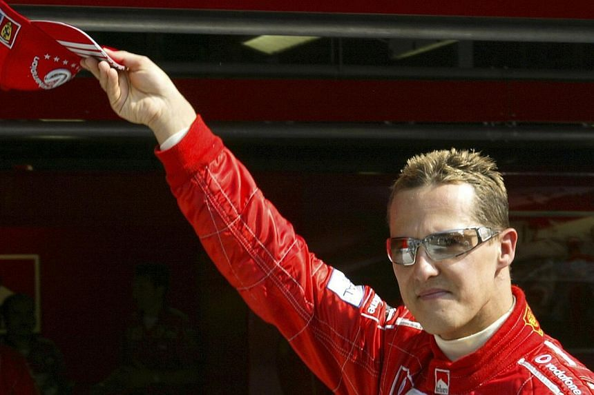 Ferrari Formula One world champion driver Michael Schumacher of Germany waves to supporters at the end of the second free practice session for the Italian Grand Prix at the Monza race track in northern Italy in this Sept 10, 2004 photo.Ferrari