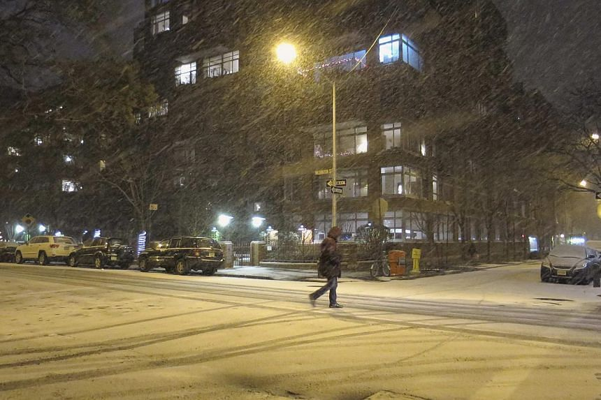 A man walks through the West Village neighbourhood as snow begins to fall in New York on Jan 2, 2014. The governors of New York and New Jersey declared a state of emergency and urged residents to stay indoors as a major winter storm hit the north-eas