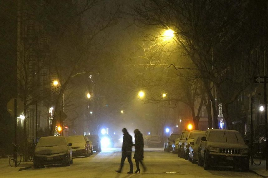People walk through the West Village neighbourhood as snow begins to fall in New York on Jan 2, 2014. The governors of New York and New Jersey declared a state of emergency and urged residents to stay indoors as a major winter storm hit the north-eas