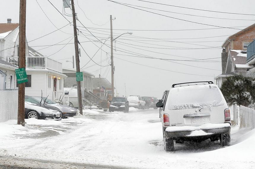 Winds whip snow from the beach across Winthrop Shore Drive Jan 2, 2014 in Winthrop, Massachusetts. An overnight blizzard is due to hit along the north-east United States on Jan 3, bringing heavy snow and delaying or cancelling thousands of flights. -