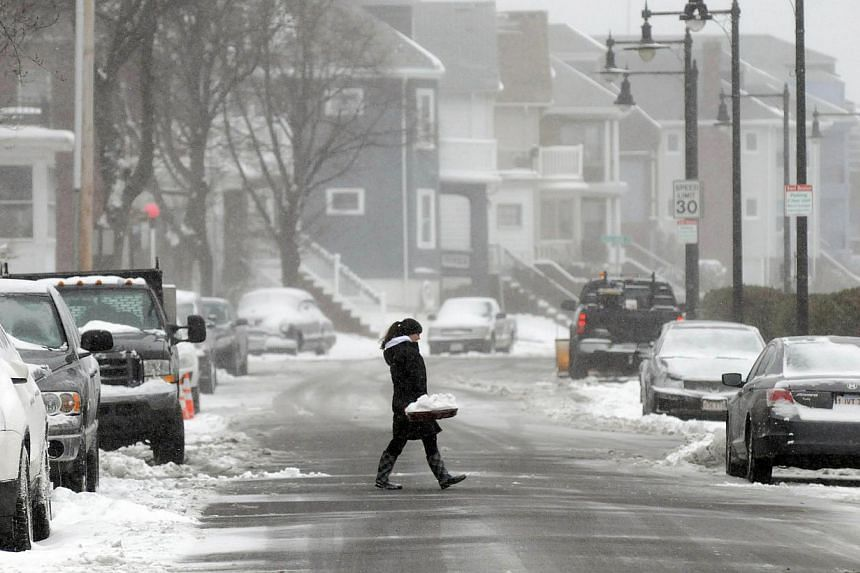 A woman carries a shovel full of snow on Bayswater Street in East Boston, Massachusetts, on Jan 2, 2014. Snowfall in the north-eastern United States caused flight cancellations and airport delays while federal government offices and schools closed du