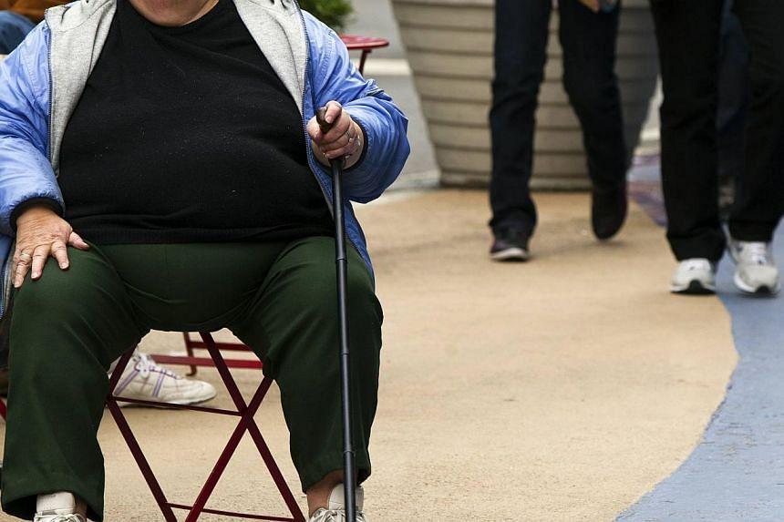 An overweight woman sits on a chair. Obesityis a major risk factor for heart disease, certain cancers and diabetes. -- PHOTO: REUTERS