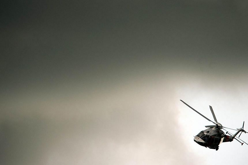 An AgustaWestland helicopter flies through a gap in the clouds during a flying display at the third day at the Farnborough International Airshow in Hampshire, southern England. -- PHOTO: AFP
