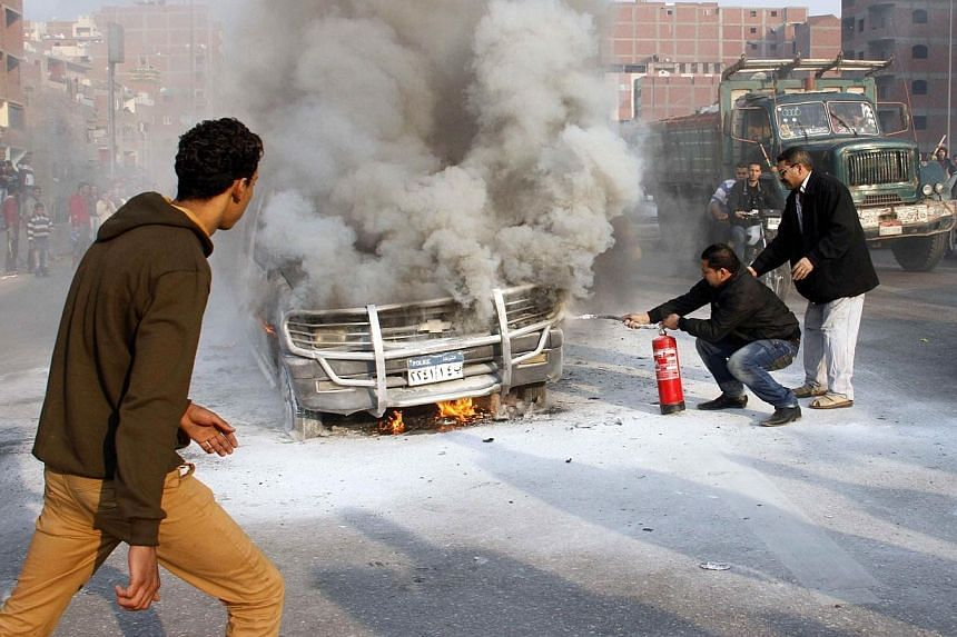 Egyptians try to extinguish a police vehicle set on fire by Muslim Brotherhood supporters on a ring road in the capital, Cairo, on Jan 3, 2014, as thousands of protesters backing deposed president Mohamed Morsi rallied across the country before polic