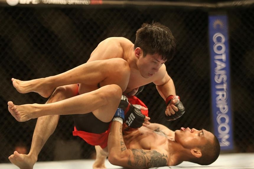 Royston Wee of Singapore punches Dave Galera of the Philippines while holding him to the ground in their UFC Fight Night Singapore bantamweight bout at Marina Bay Sands on Jan 4, 2014. -- ST PHOTO: KEVIN LIM