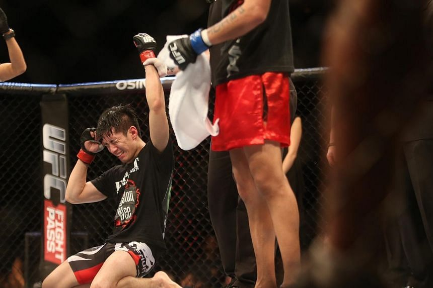 Royston Wee of Singapore drops to his knees after being announced the winner against Dave Galera of the Philippines in UFC Fight Night Singapore bantamweight bout at Marina Bay Sands on Jan 4, 2014. -- ST PHOTO: KEVIN LIM