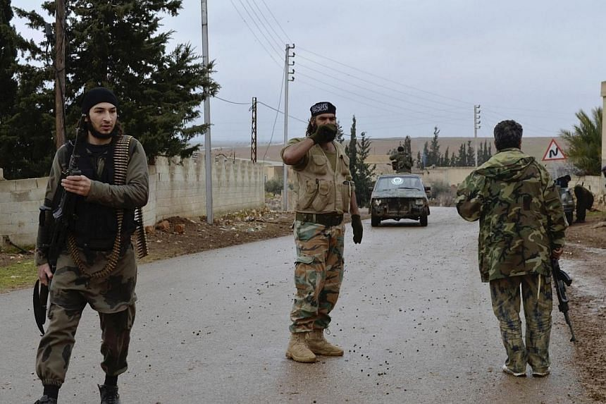 """Free Syrian Army fighters are seen along a street in Hama province on Dec 31, 2013.Syria's main opposition National Coalition said on Saturday, Jan 4, 2014, it """"fully supports"""" rebels fighting a powerful Al-Qaeda affiliate in northern Syria, tw"""