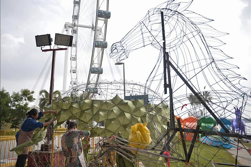 Craftsmen Liu Hong (left), 38, and Li Huiyu, 46, from China's Sichuan province putting together the durian-shaped lantern yesterday for the River Hongbao. There will be 28 large handmade lantern displays at this year's carnival, to be held at the Flo