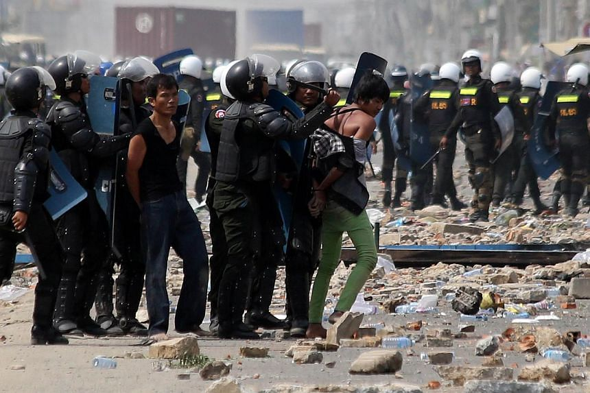 Cambodian military police arrest protesters during a garment workers protest to demand higher wages in front of a factory in Phnom Penh on Jan 3, 2014.The United States (US) on Friday appealed for peaceful dialogue and denounced violence in Cam