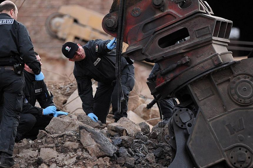 Criminal investigation officers examine a damaged excavator at the accident site of an exploded World War II bomb in Euskirchen, western Germany, on Jan 3, 2014.The driver of an excavator was killed and 13 other people injured when a World War