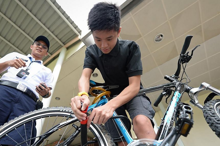 Pasir Ris resident, Oston Yong, 16, tries out the new lock ahead of the 'U-Lock or U Lose' launch on Jan 4, 2014. Officers from Pasir Ris Neighbourhood Police Centre are putting the brakes on bicycle theft with the 'U-Lock or U Lose!' campaign. -- ST
