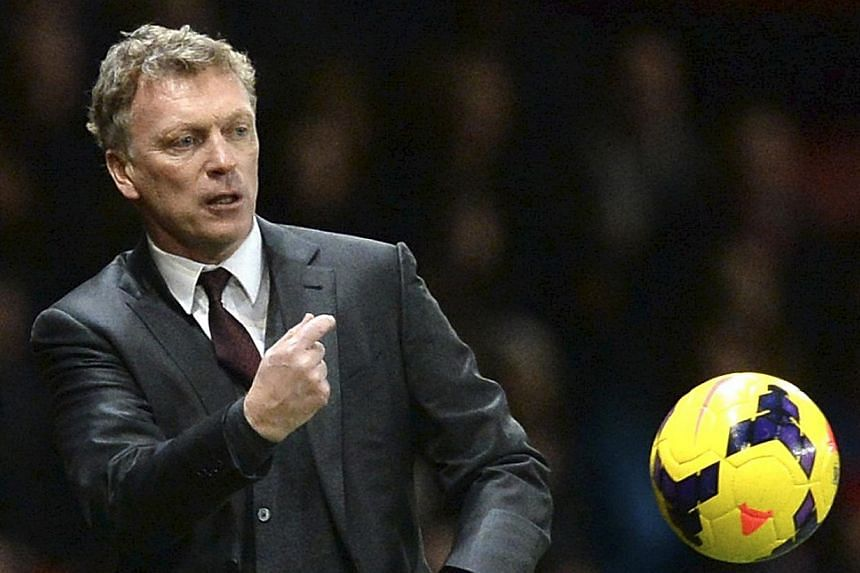 Manchester United manager David Moyes throws the ball back onto the pitch during their English Premier League soccer match against Tottenham Hotspur at Old Trafford in Manchester, northern England, on Jan 1, 2014. Moyes heads into Sunday's FA Cup thi