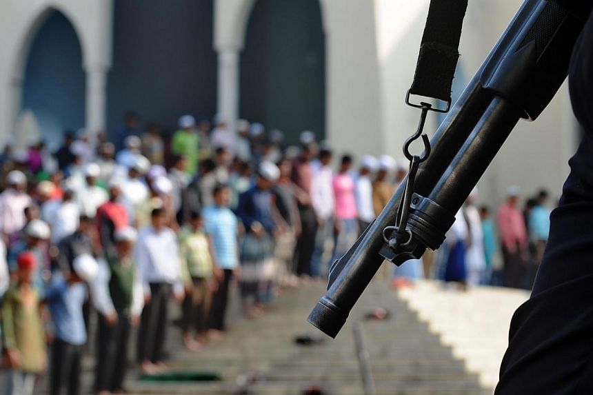 People take part in Friday prayers as members of the police stand guard in Dhaka on Jan 3, 2014.Bangladesh's opposition began enforcing a 48-hour general strike on Saturday on the eve of elections as its leader remained confined to her home. --